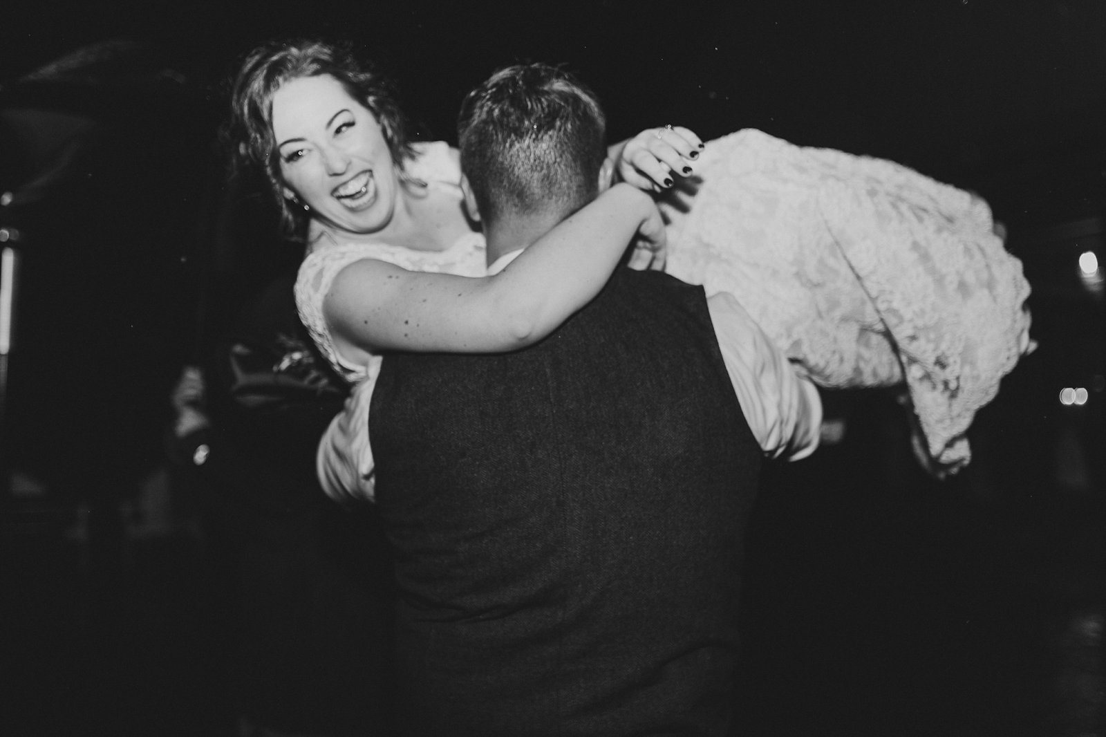 Groom Carrying Bride in Black and White Wedding Photography