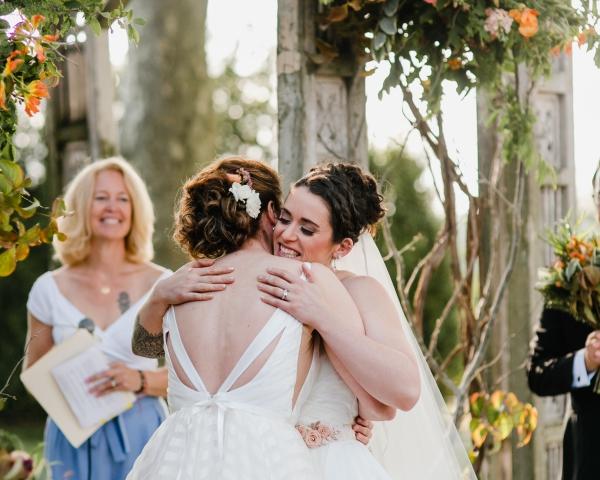 Brides hugging at same sex wedding in Philadelphia PA