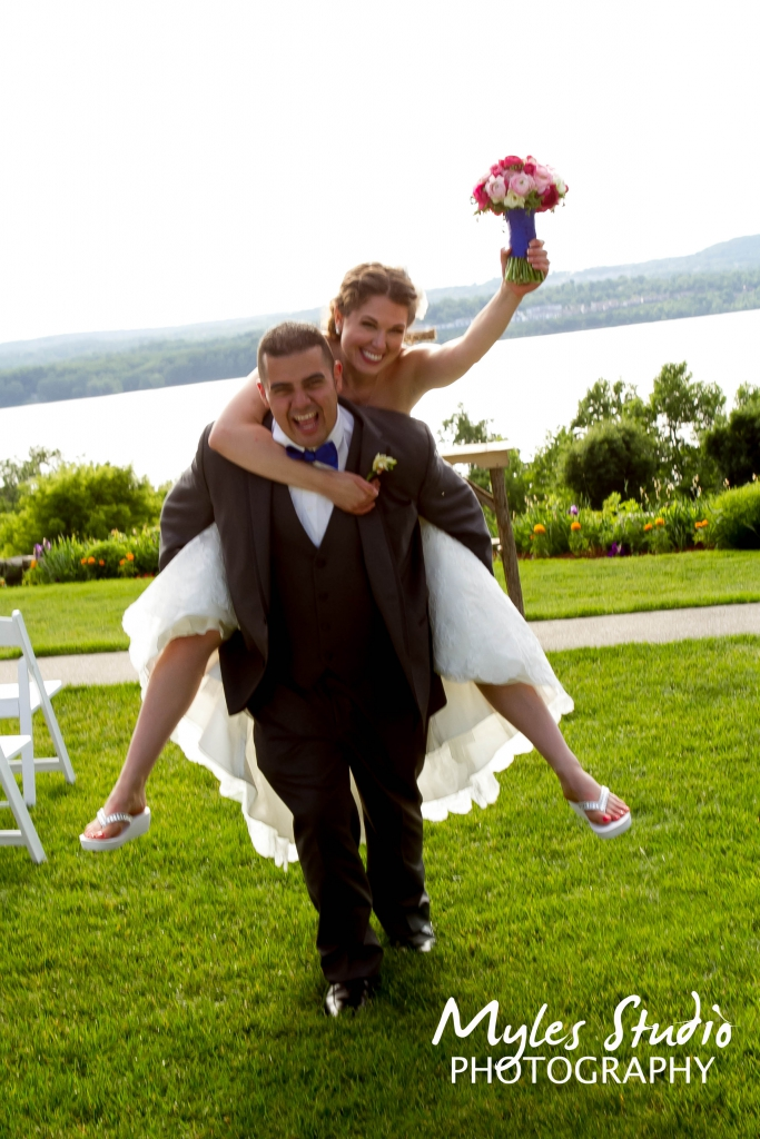 Bride and Groom celebrating their wedding with a piggy back ride, taken at the Dutchess Manor in Beacon NY.