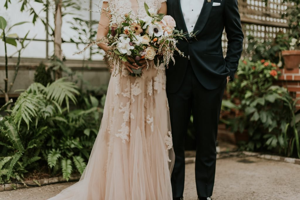 Groom in black tux with bride in blush lace and organic bouquet