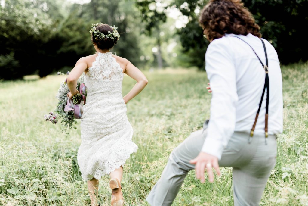 Boho bride and groom running through field at Awbury Arboretum Wedding