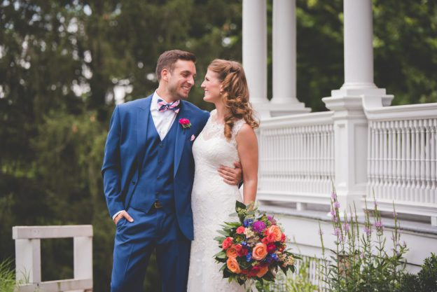 Bride in lace gown holding bold floral bouquet with groom in blue suit and striped bowtie at John James Audubon Center at Mill Grove Wedding