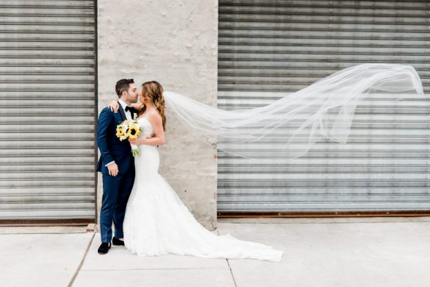 Bride's cathedral veil blowing in the wind during portraits at Front + Palmer wedding