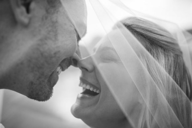 Bride and Groom kiss under veil at Spring Mill Manor Wedding