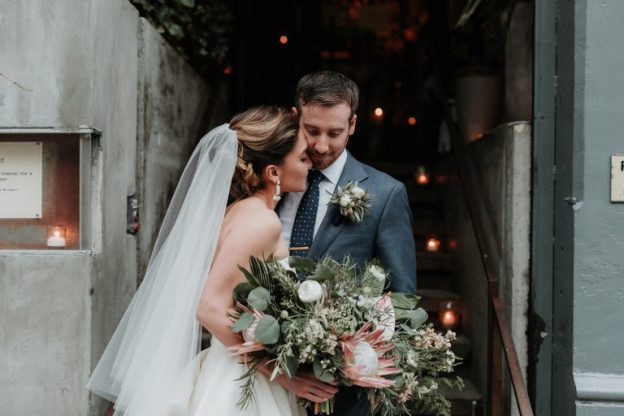 Bride holding stunning bouquet with groom at Public NYC wedding