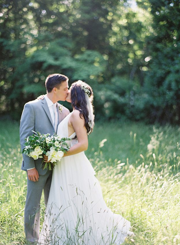 Bride and Groom kiss in a field during portraits at Deer Park Campground Wedding