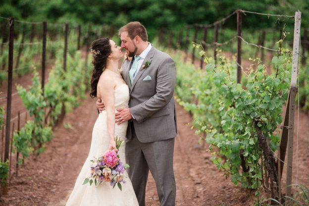 Bride and groom share a kiss in the vineyard at their Sand Castle Winery Wedding