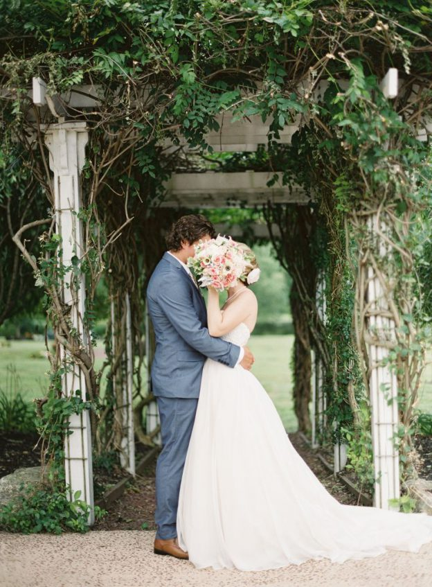 Bride and groom beneath vine-covered arbor at Brandywine Manor House Wedding