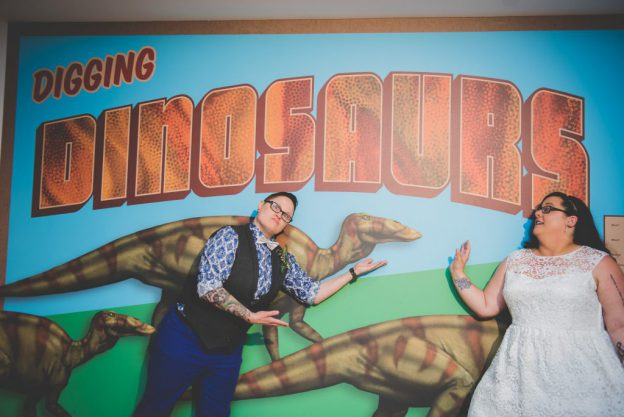 Same sex couple in front of dinosaur mural at Morris Museum Wedding