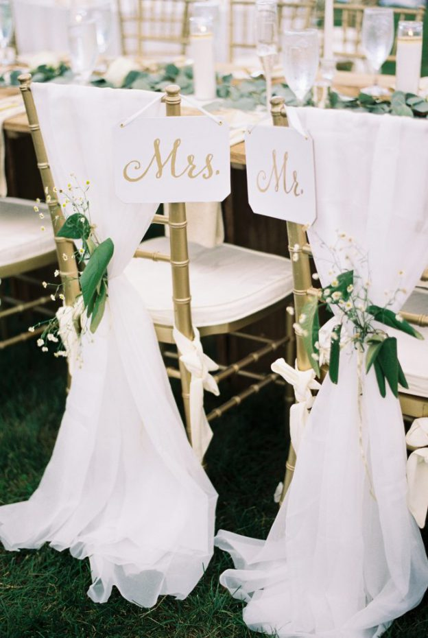 Mr. and Mrs. Chair signs with white draping and flowers at Wedding at Paxson Hill Farm