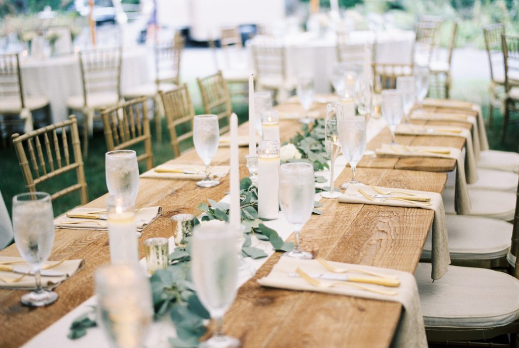 Tent wedding with barn table with green and white tablescape and gold garden chairs. Photo by Du Soleil Photographie.