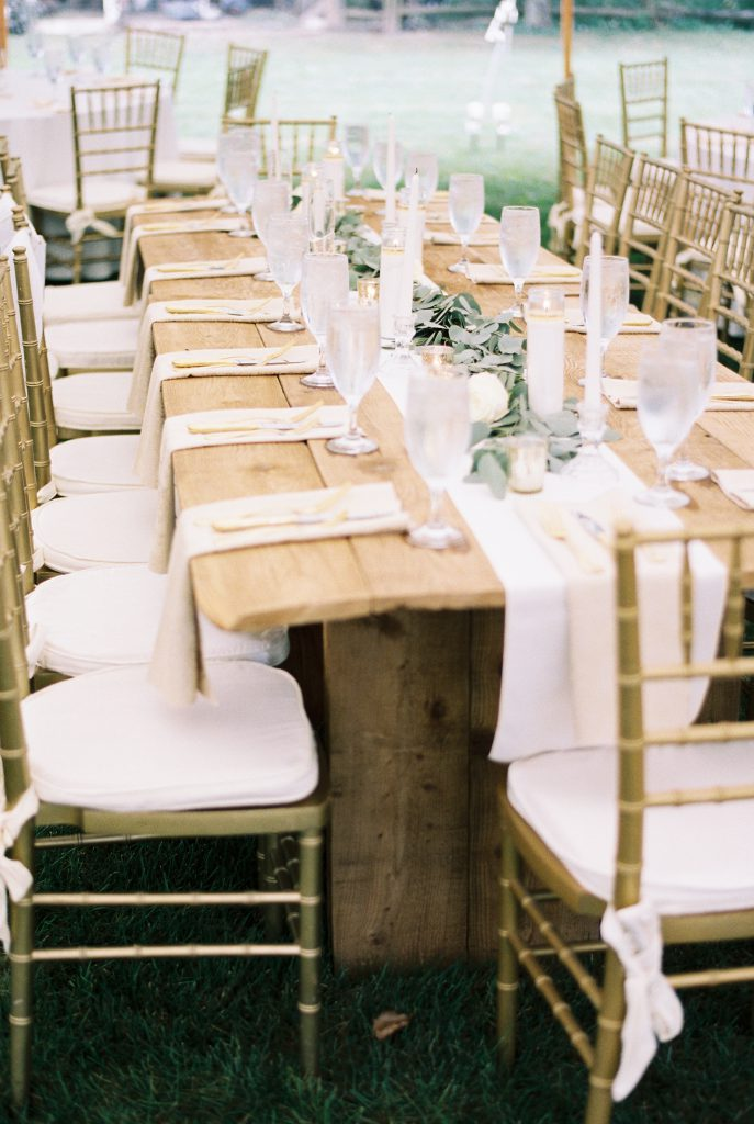 Barn farm table with greenery runner at Paxson Hill Farm Wedding. Tablescape with white runner and white candlesticks with gold garden chairs. Photo by Du Soleil Photographie.