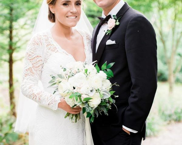 V-Neck, long sleeve, lace wedding gown with Groom in black tuxedo. Photo by Du Soleil Photographie.