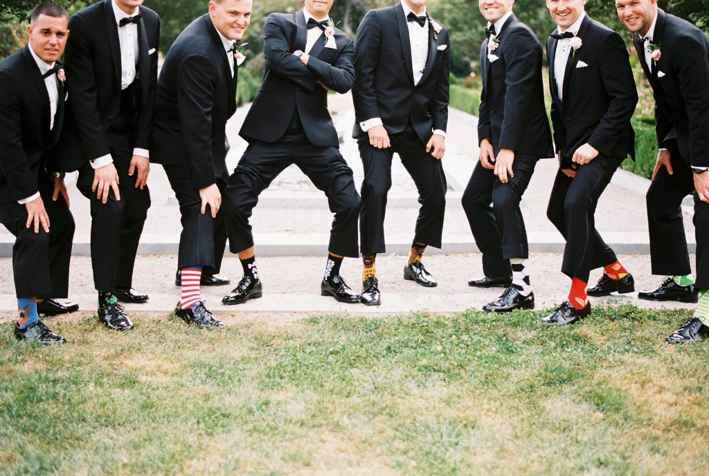 Groomsmen in black tuxedo and bowties with fun socks. Photo by Du Soleil Photographie.