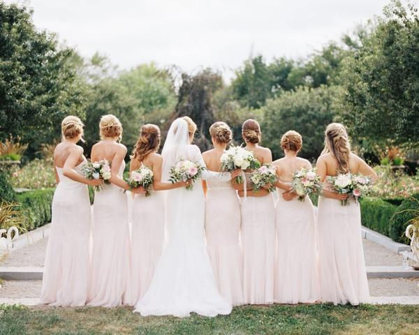 Bride and bridesmaids in garden at Paxson Hill Farm. Blush Bridesmaids dresses and pink, white, and green flowers. Photo by Du Soleil Photographie.