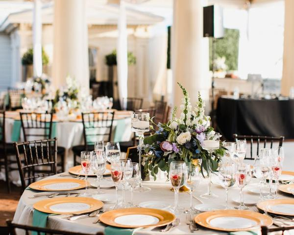 Round Tables at Philadelphia Water Works Wedding. Gold plates with purple, white, and blue floral centerpieces. Photo by Love Me Do Photography.