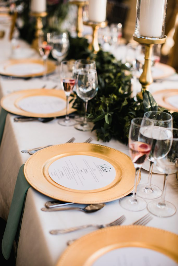 Tablescape with round menus on gold plate chargers for a classic wedding at Philadelphia Water Works. Greenery table runner by Robertson's Flowers & Events and photo by Love Me Do Photography.