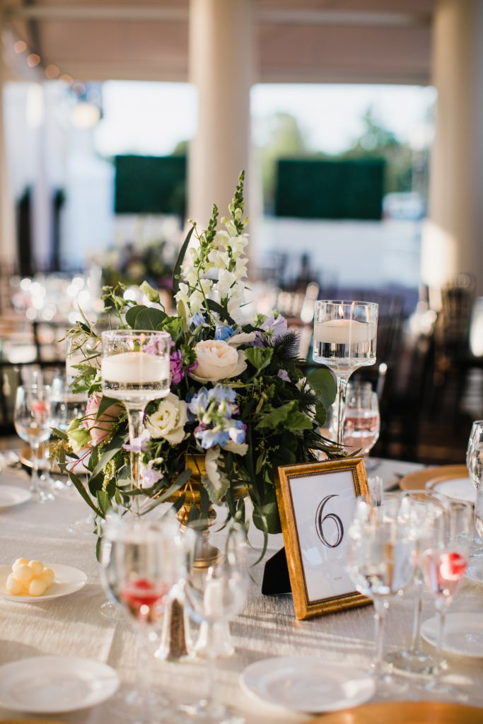 Robertson's floral centerpiece with green, blue, purple and light pink flowers and gold accents. Photo by Love Me Do Photography.