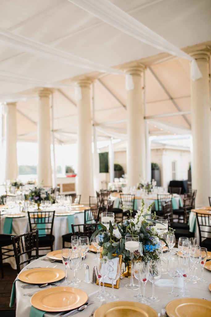Draping and round table arrangement with garden chairs and gold chargers at Philadelhpia Water Works wedding. Green, blue, purple and white floral centerpieces by Robertson's Flowers & Designs and photo by Love Me Do Photography.