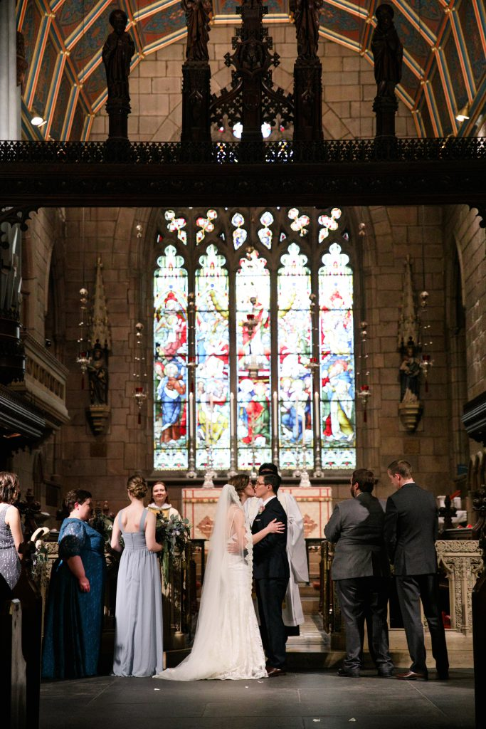 Wedding at St. Mark's Episcopal Church in Center City Philadelphia. Bride and Groom kiss with stained glass windows behind them. Photo by Love Me Do Photography.