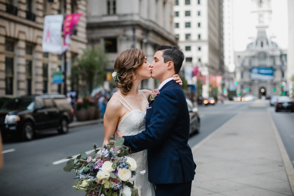Bride and groom kissing on Broad Street in front of Philadelphia City Hall. Florals by Robertson's Flowers & Events and photo by Love Me Do Photography.
