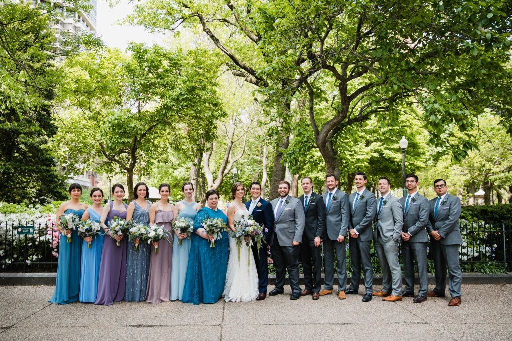 Different styles and shades of blue, purple and grey Bridesmaids dresses and Groomsmen suits. Wedding bouquets by Robertson's Flowers & Events and photo by Love Me Do Photography in Philadelphia city park.