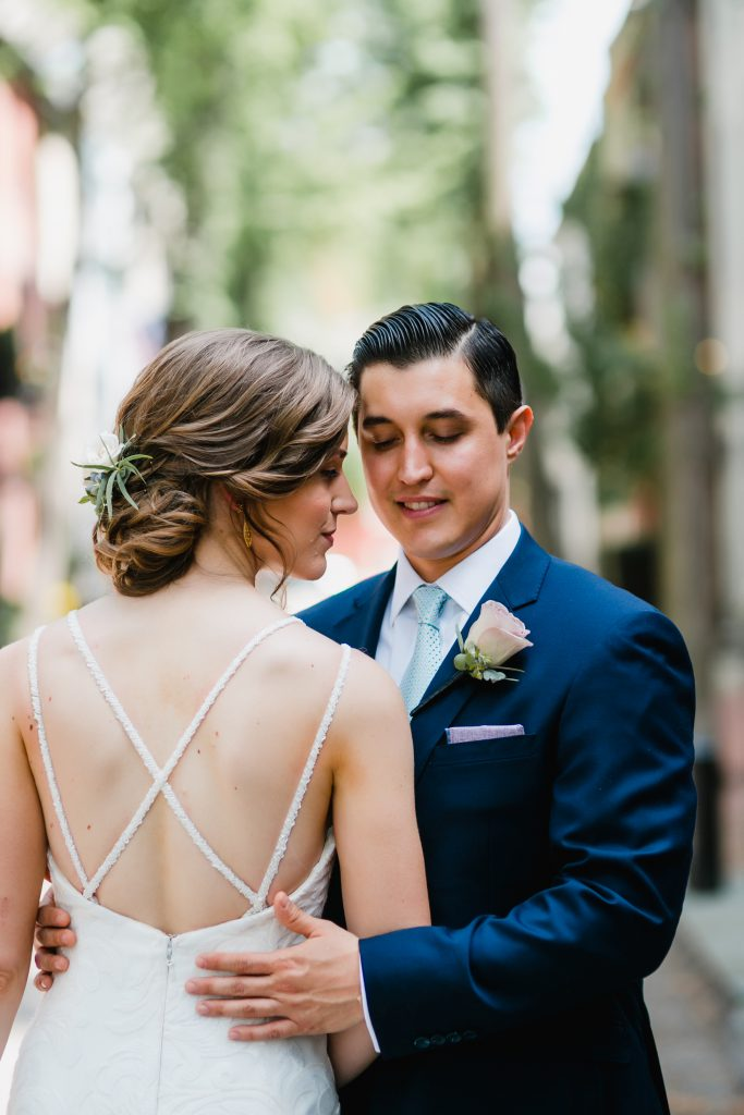 Bride in strappy low back wedding dress and loose romantic hair. Groom in navy suit and pink rose boutonniere. Photo by Love Me Do Photography in Philadelphia.