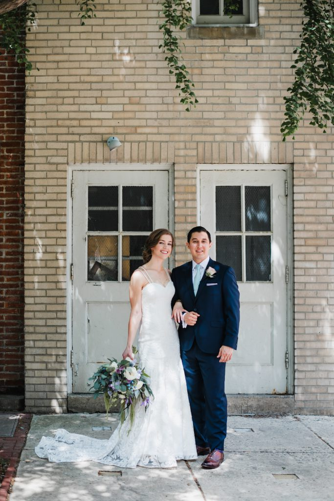 Philadelphia Bride and Groom taking wedding portrait in Center City. Bride in lace wedding dress holding bouquet of purple, blue, turquoise, and white flowers by Robertson's Flowers & Designs. Groom in Navy suit and brown dress shoes. Photo by Love Me Do Photography in Philadelphia.