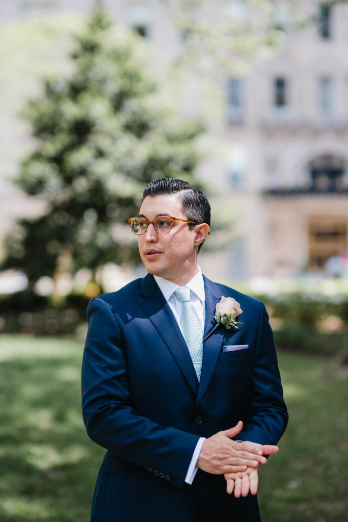 Modern Groom in navy suit with pink rose boutonniere with light purple pocket square. Photo by Love Me Do Photography in Philadelphia.