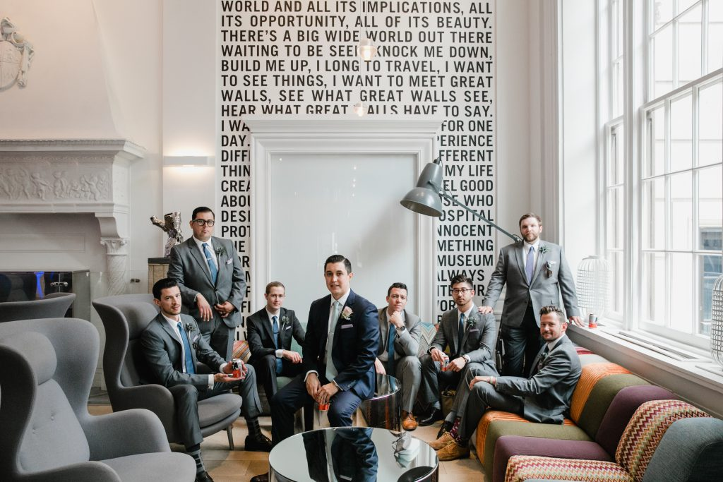 Modern Groom and Groomsmen in grey suits with blue ties in front of black and white quote wall at The Warwick Hotel Rittenhouse Square in Philadelphia. Photo by Love Me Do Photography.