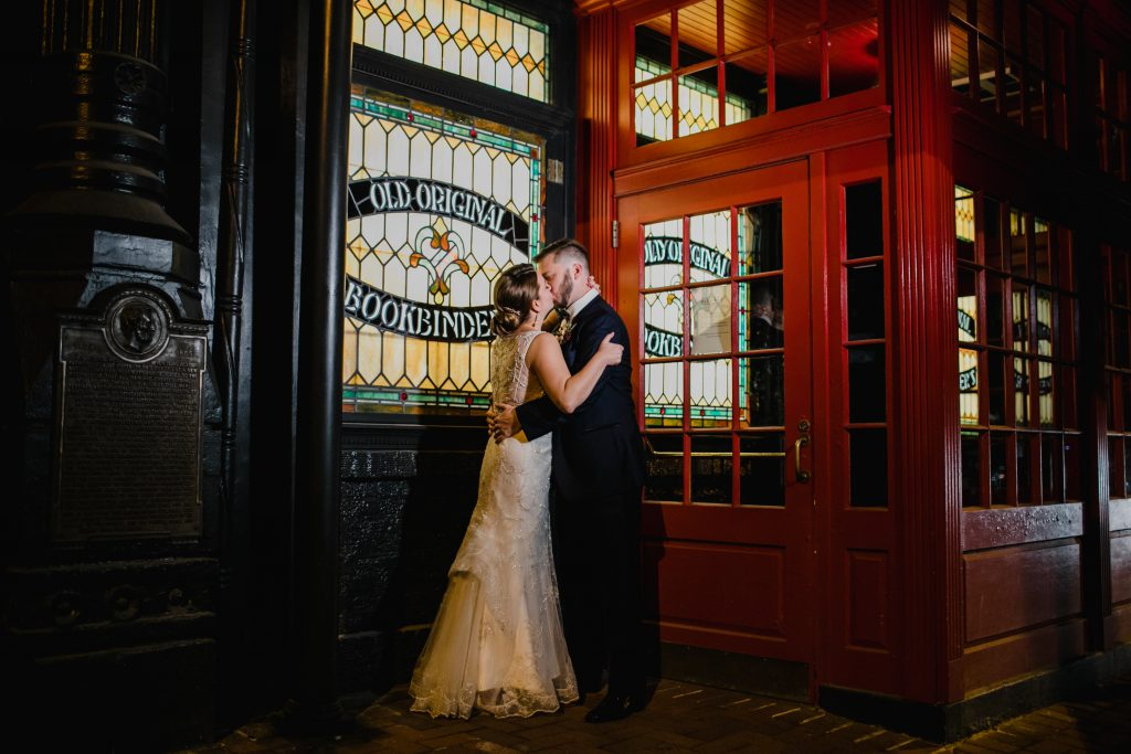Bride and Groom kiss outside of their wedding reception at The Olde Bar in Philadelphia. Stained glass and red door are the backdrop. Photo by Love Me Do Photography.