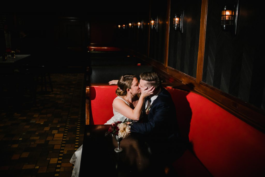 Bride and Groom kiss in red booth at The Olde Bar where they held their wedding reception in Philadelphia. Photo by Love Me Do Photography.