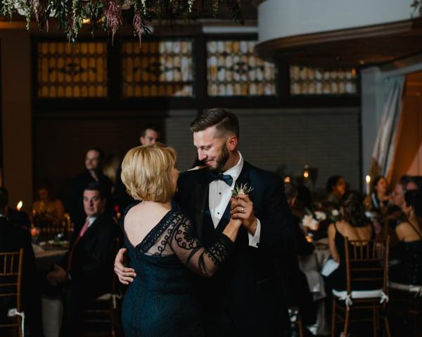Groom dances with his mother under flower chandelier at The Olde Bar Wedding, a Garces Group Restaurant. Photo by Love Me Do Photography.