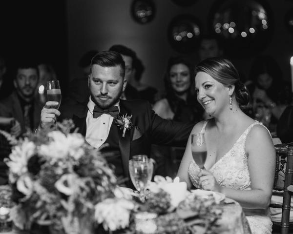 Bride and Groom toast at their wedding reception at The Olde Bar Philadelphia. Photo by Love Me Do Photography.