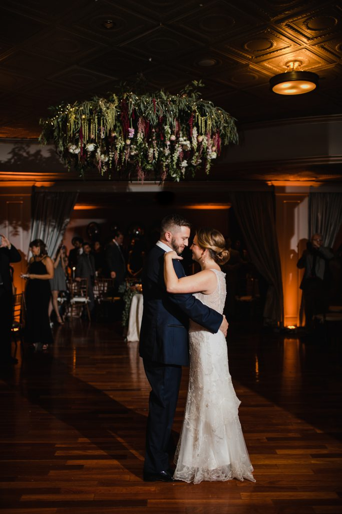 Large flower chandelier at wedding reception at The Olde Bar in Philadelphia. Flowers by A Garden Party and photographed by Love Me Do Photography.