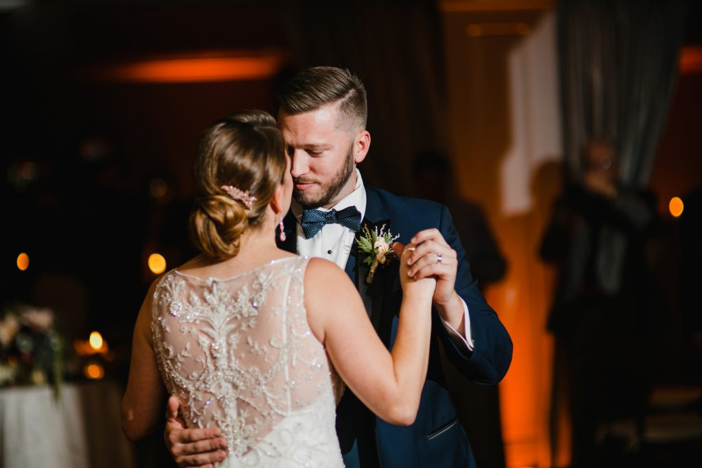 Elegant low bun wedding hair with pink crystal hairpiece by True Beauty Marks in Philadelphia. Bride and Groom dance at their wedding reception at The Olde Bar. Photo by Love Me Do Photography.