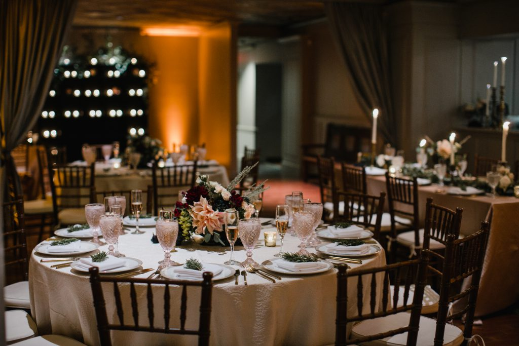 Romantic wedding at The Olde Bar Philadelphia, a Garces Events Restaurant. Circular tables with print table clothes and pink and maroon floral centerpieces. Photo by Love Me Do Photography.