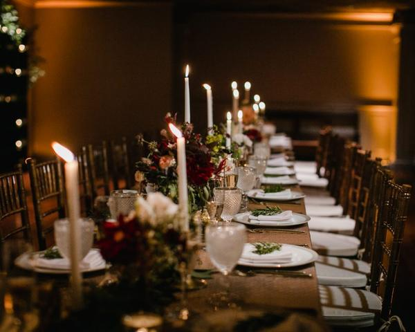 Romantic tablescape with white candles, gold candlesticks and maroon, pink and green floral centerpieces. Wedding at The Olde Bar Philadelphia, a Garces Group Restaurant. Photo by Love Me Do Photography.