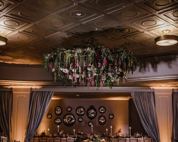 Flower chandelier over sweetheart table at wedding at The Olde Bar in Philadelphia, a Garces Group Restaurant. Wedding decor of purple, pink, green flowers by florist, A Garden Party. Photo by Love Me Do Photography.