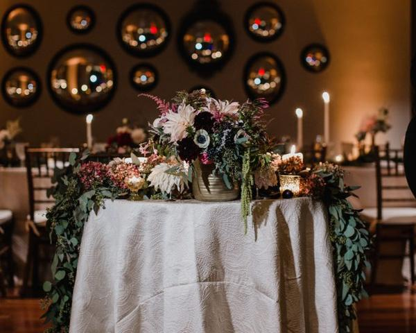 Round Sweetheart Table Decor with pink, dark purple, maroon, and green flowers by A Garden Party at The Olde Bar Philadelphia. Photo by Love Me Do Photography.
