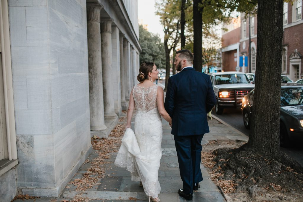 Bride in wedding dress with beaded back walking with Groom in Philadelphia. Wedding Photo by Love Me Do Photography.
