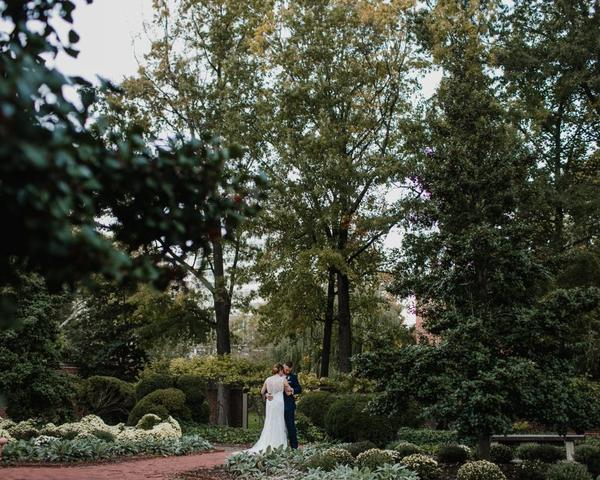 Bride and Groom in 18th Century Garden in Philadelphia for Fall wedding. Wedding Photo by Love Me Do Photography.