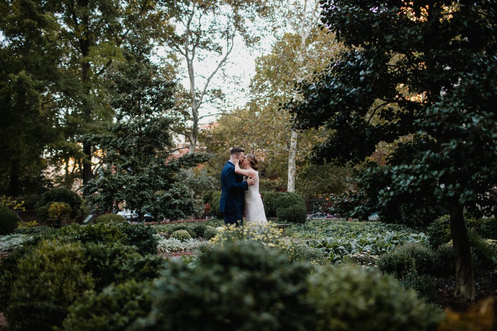 Bride and Groom kiss for wedding photo in 18th Century Garden in Philadelphia. Wedding photo by Love Me Do Photography.