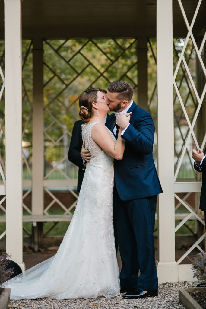 Bride and Groom kiss during wedding ceremony under gazebo in 18th Century Garden. Photo by Love Me Do Photography.
