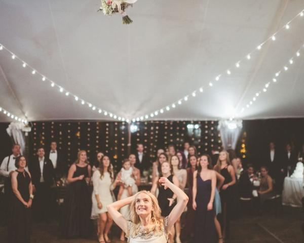 Bouquet toss at The Inn at Barley Sheaf Farm Wedding Farm wedding. Fall wedding in outdoor white tent with Edison lights. Photo by Paper Antler shared by The Styled Bride.