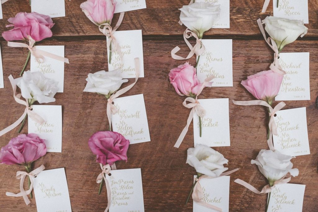 Flower adorned calligraphy escort cards at Inn at Barley Sheaf Farm Wedding. Photo by Paper Antler. Shared on Flutter Social by The Styled Bride