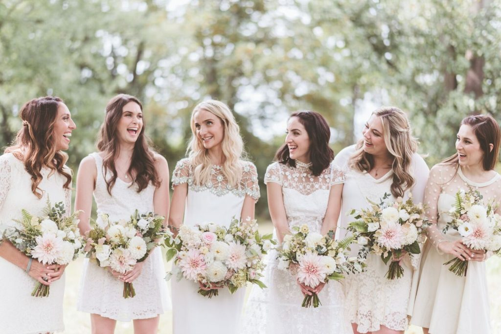 Bride and bridesmaids in mismatched white dresses holding blush bouquets. Photo by Paper Antler. Shared on Flutter Social by The Styled Bride