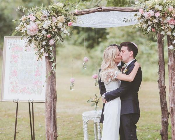 Newlyweds Kiss Under Flower-Adorned Chuppah at Inn at Barley Sheaf Farm Wedding. Photo by Paper Antler. Shared on Flutter Social by The Styled Bride