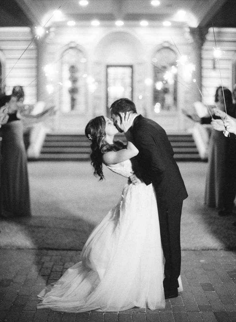 Ashford Estate bride in Monique Lhuillier gown and groom in black tux kiss during sparkler send-off. Photo by Rebecca Yale. Shared on Flutter Social by The Styled Bride