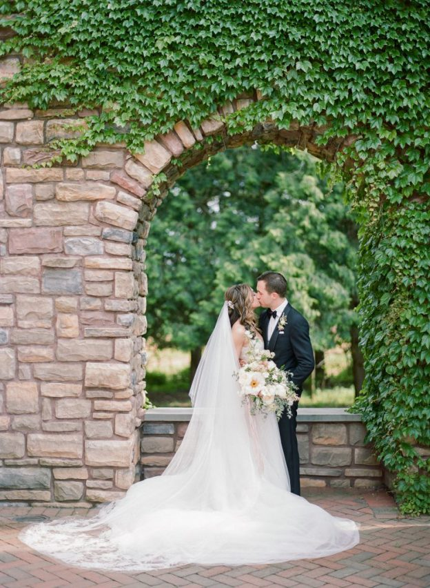 Bride and groom in front of ivy-covered arch at Ashford Estate Wedding